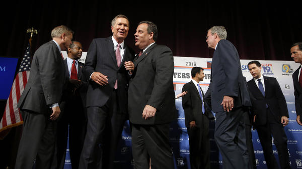 Republican presidential candidates, from left, Lindsey Graham, Ben Carson, John Kasich, Chris Christie, Bobby Jindal, Jeb Bush, Scott Walker and Rick Santorum speak among themselves after a forum Monday, Aug. 3, 2015, in Manchester, N.H.
