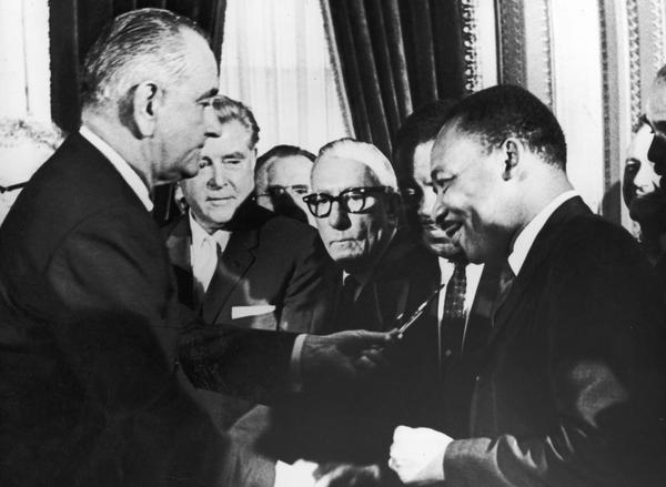 U.S. President Lyndon B. Johnson hands a pen to civil rights leader Rev. Martin Luther King Jr. during the the signing of the voting rights act as officials look on behind them, Washington, D.C., August 6, 1965. (Washington Bureau/Getty Images)
