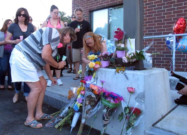 People place flowers Sunday at the site of the shooting of social worker Lara Sobel.