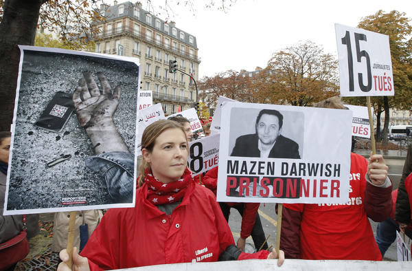 Lucie Morillon, head of research at French watchdog of Reporters Sans Frontieres (Reporters without Borders) holds a banner depicting Syrian human rights activist Mazen Darwish during a protest against violence in Syria, in Paris, Saturday, Oct. 20, 2012. Darwish was released from a Syrian prison Monday.