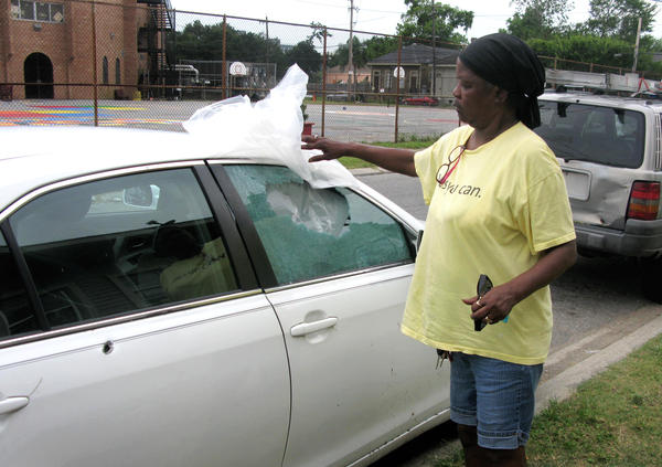 Debra Hunter shows off the bullet holes and damage to her car after a gunfight near her New Orleans home. Police say one of the two people arrested used an AK-47 assault rifle in the incident, which occurred on a weekday during lunch hour, not far from a police station and New Orleans City Hall.