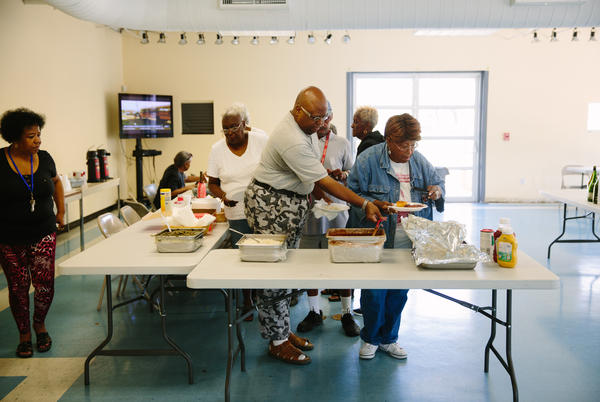 Patrons of the Sojourner Truth Community Center in the Faubourg Lafitte housing development help themselves to free red beans and rice and greens. The center provides a community space for the development and programs to encourage interaction between residents.