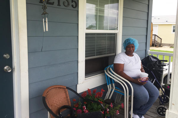 Seafood worker Stephanie Baker, still wearing a blue hairnet after getting off work, catches a breeze on her front porch in Safe Harbor, a neighborhood of manufactured homes built with disaster relief funds after Hurricane Katrina. Residents say rents have been escalating since the storm.