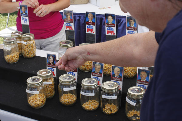 "Iowa State Fair visitors place corn kernels in the jar of the candidate of their choice during an informal ""corn poll"" in 2011."