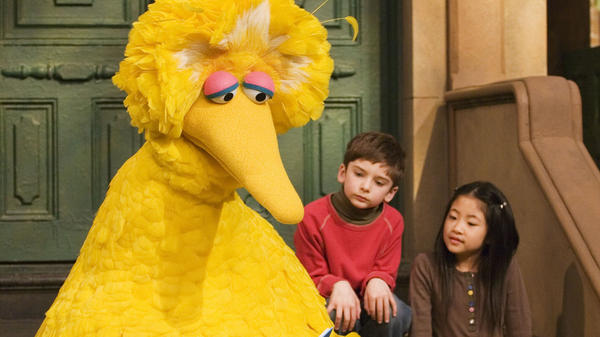 Big Bird, played by puppeteer Caroll Spinney, reads to Connor Scott and Tiffany Jiao during a taping of <em>Sesame Street</em> in 2008 in New York.