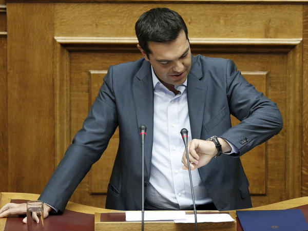 Greek Prime Minister Alexis Tsipras looks at his watch as he speaks to a marathon parliamentary session in Athens on Friday. A bitterly divided Parliament approved a draft bailout agreement with international lenders.