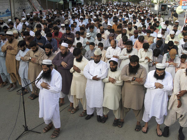 Supporters of the Pakistani group Jamaat-ud-Dawa, declared a terrorist organization by the United Nations, offer funeral prayers in Karachi, Pakistan, after the death of  Taliban leader Mullah Omar was announced recently.