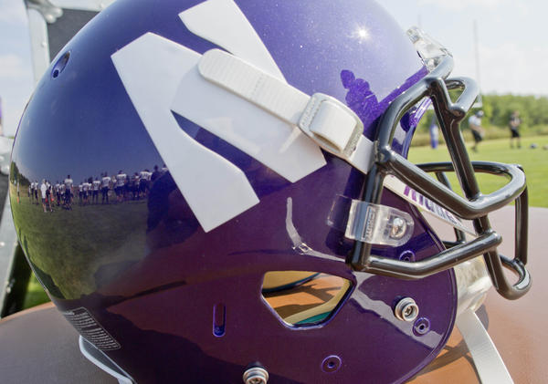 Northwestern football players are reflected in a helmet during drills at a practice. On Monday, the National Labor Relations Board dismissed a petition that players be allowed to form a union.