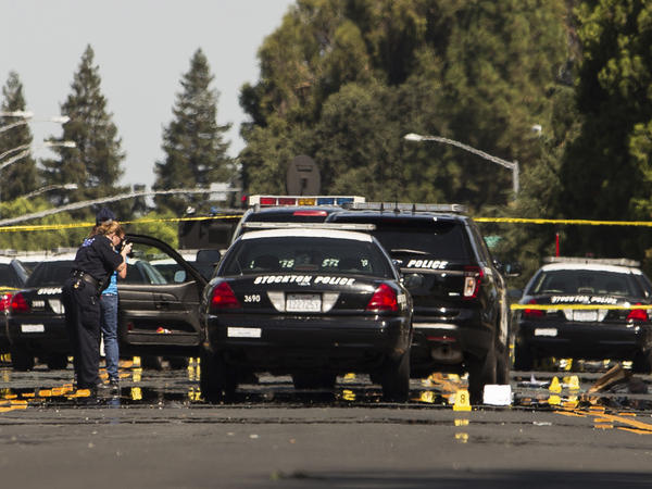 Investigators examine the scene of the police pursuit's conclusion  in Stockton, Calif., on July 17, 2014.