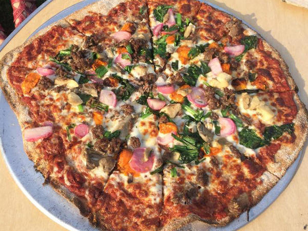 Five veggie (roasted radishes, broccoli raab, mixed farm mushrooms, scallions and cherry tomatoes) with sausage pizza from Stoney Acres Farm.