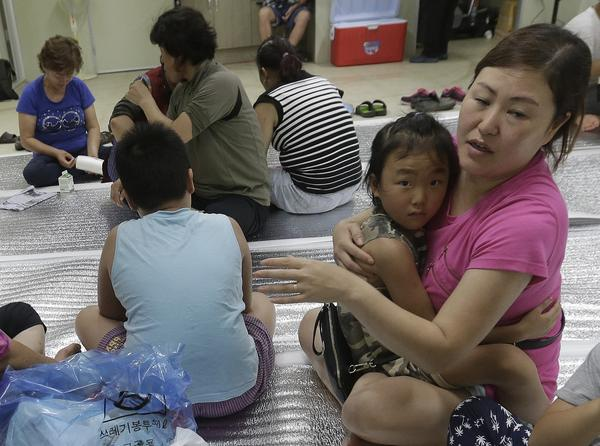 South Korean residents gather at a shelter in the South Korean town of Yeoncheon where one shell fell on Thursday.