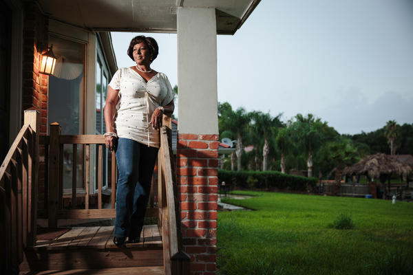 Attorney Ermence Parent stands on the porch of her New Orleans home. Two hip replacements eased Parent's pain and got her exercising again, she says. A doctor at one of the city's newly renovated clinics made the diagnosis.