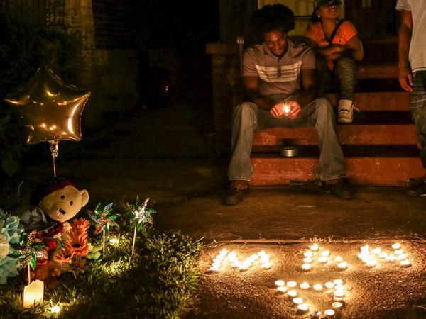 Chris Ball-Bey, the brother of Mansur Ball-Bey, sits by his brother's memorial after a candlelight vigil on Walton Avenue in St. Louis.