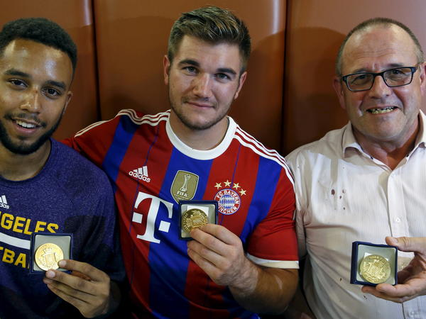 Three men who helped to disarm an attacker on a train from Amsterdam to France, from left to right, Anthony Sadler, Alek Skarlatos and Chris Norman, a British man living in France, pose with medals they received for their bravery at a restaurant in Arras, France. A fourth man, American Spencer Stone, was wounded in the take-down and remains in the hospital.