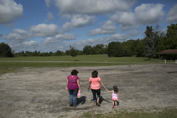 Beth Carey (center), walks around the park with her nieces Calysta Dildine, 15, and Jazlen Harden, 3, in Marion. Chrystina, Beth's twin sister and Jazlen and Calysta's mother, died of a drug overdose in February of 2013.