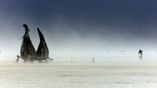 A bicycle rider makes it through a dense sandstorm during the Burning Man Festival in 2000. Hail, wind and dust storms are regular occurrences at the festival — and for a while, there were fears that this year's celebration would also include an infestation of bugs.