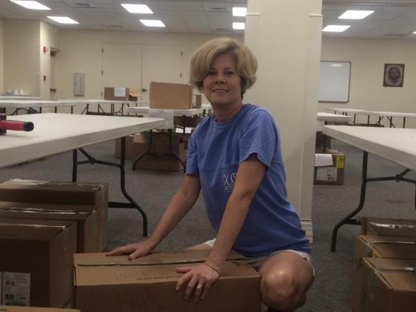 Lizbeth Engle packs boxes of clothing.