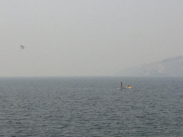 Paddle boarders try to enjoy what's left of summer, even with very smokey skies over Lake Chelan.