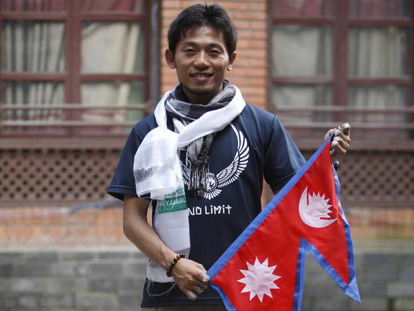 Japanese climber Nobukazu Kuriki poses with a Nepalese flag during a news conference in Kathmandu, Nepal, on Sunday. He will begin his fifth attempt to climb Mount Everest on Tuesday.