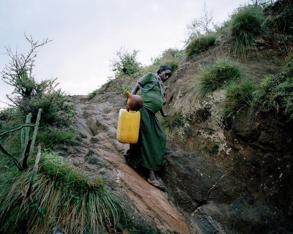 Uchiya, who is 29 and eight months pregnant, carries an empty jerry can from her mountaintop home to a source of water below. She'll fill it with 5 gallons and then climb back up. In sub-Saharan Africa, women spent 40 billion hours a year collecting water.
