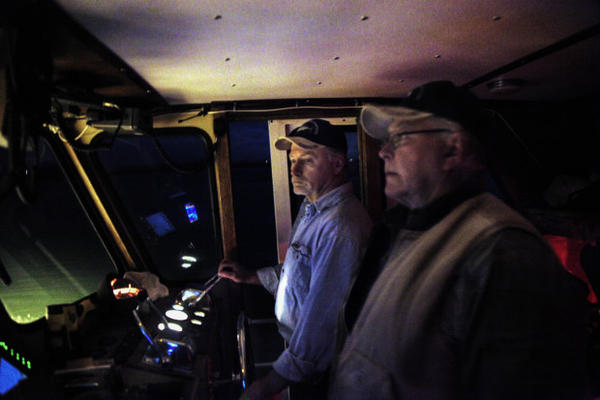<p>Milton Gudgell, right, and his son Rob Gudgell on a nighttime boat ride to East Sand Island.</p>
