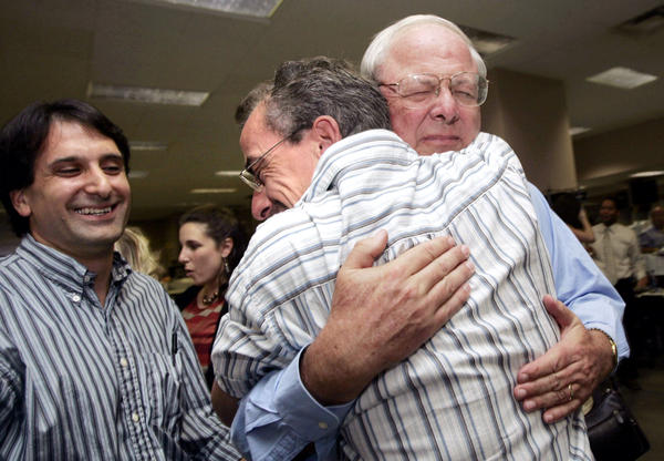 Ashton Phelps Jr. (facing camera), publisher of the <em>Times-Picayune</em> in New Orleans, hugs columnist Chris Rose after learning the paper won two Pulitzer Prizes on April 17, 2006.