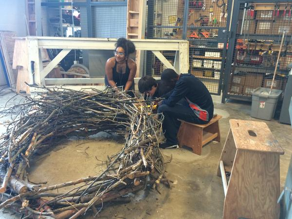 Designer Rochelle Crosby works with 13 year-old Adrian Vasquez on the human-size bird nest
