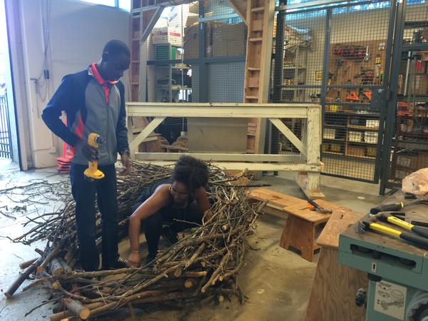 Rochelle Crosby of DownCity Design helps Adrian Vasquez build a bird nest for a preschool playground