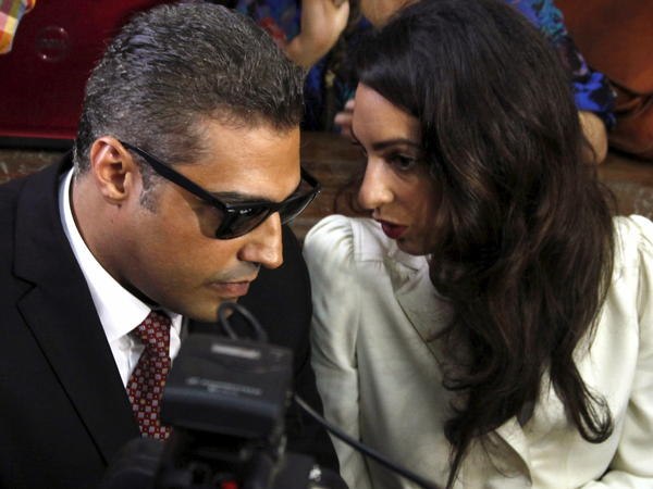 Al-Jazeera English television journalist Mohamed Fahmy talks to his lawyer Amal Clooney before hearing the verdict at a court in Cairo, Egypt, on Saturday. Fahmy and two others were sentenced to three years in prison on terrorism-related charges.