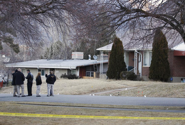 Investigators stand next to evidence markers in front of the house of Matthew Stewart, who was shot and injured by Ogden police during a drug raid, in Ogden, Utah, Jan. 5, 2012. One police officer was killed and five were wounded in the shootout that erupted as a narcotics enforcement team executed a search warrant at Stewart's home.