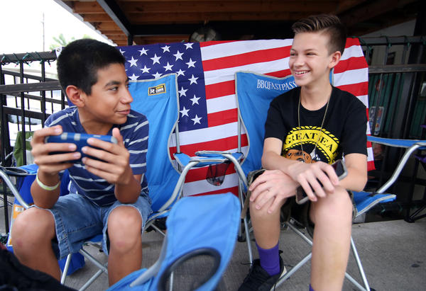 Desmond Roldan (right) is the 13-year-old behind BBQ Fast Pass, the line-sitting service. He's seen here with his friend Jiovani Acosta on July 3.