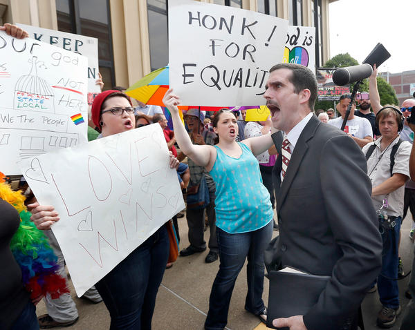 Street preacher Jeffrey Shook, with Unity Baptist Church in Hickory N.C., preaches to Kim Davis protesters in front of the Carl D. Perkins Federal Building in Ashland, Ky., Thursday. Same-sex couples in Rowan County began marrying Friday — but Davis' lawyers say those licenses are invalid.