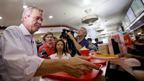 "Jeb Bush is handed a ""yellow dog"" at Varsity Drive-In last month in Atlanta. That's a hot dog with mustard."