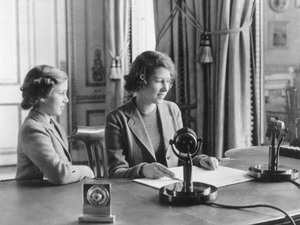 Princess Elizabeth makes her first broadcast, accompanied by her younger sister, Princess Margaret, in October 1940 in London.