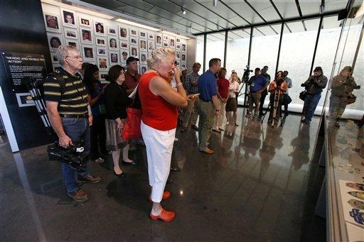 Visitors stand in front of a wall of photos of the 40 crew and passengers who perished in the crash. The center was formally dedicated Thursday.
