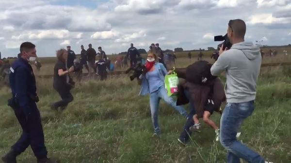 """Camerawoman Petra Laszlo trips a migrant holding a young boy as he tries to run past a police collection point in Hungary. """"I'm not a heartless, racist, children-kicking camerawoman,"""" Laszlo later said."""
