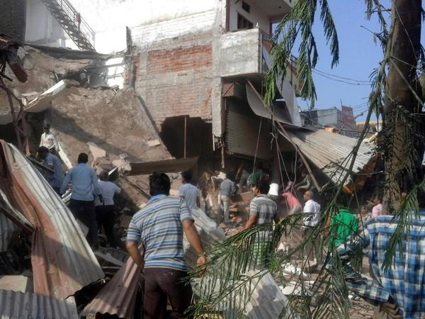 People gather at the site of an explosion in Jhabua, Madhya Pradesh, India, on Saturday. Scores of people were killed in twin blasts linked to cooking gas cylinders.