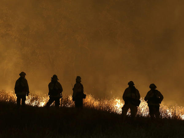 Firefighters stand guard as flames from the Butte Fire approach a containment line, on Saturday, in San Andreas, Calif.