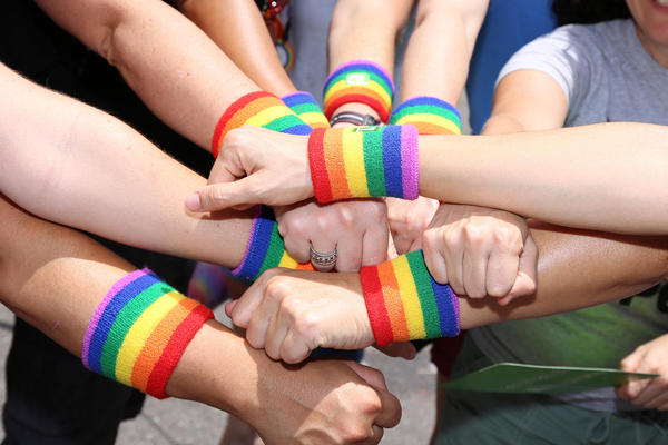 Friends at the 2015 St. Pete Pride parade show off armbands celebrating the legalization of same-sex marriage.