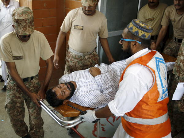 Soldiers help emergency workers wheel an injured man to a hospital after an attack by Taliban militiamen on an air force base in Peshawar, Pakistan, on Friday.