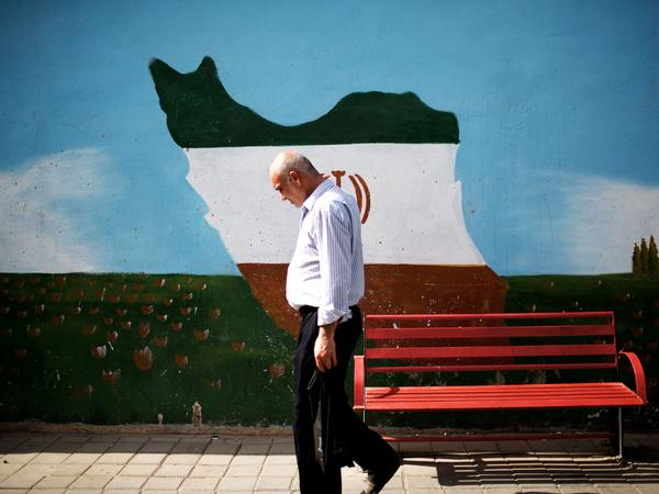 An Iranian man walks past a mural displaying an outline of Iran, adorned in the colors of the country's national flag, on June 29 in Tehran. A large majority of Iranians appears to support the nuclear deal.