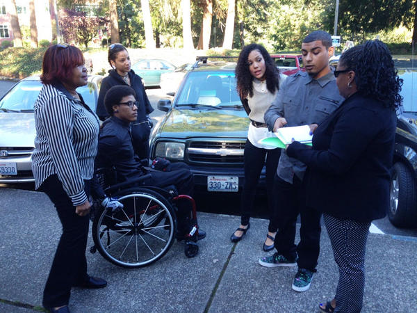 Bryson Chaplin, in wheelchair, and his brother Andre Thompson confer with family members before a court hearing in Olympia. Both men were shot by a white Olympia police officer in May and have pleaded not guilty to charges of felony assault.