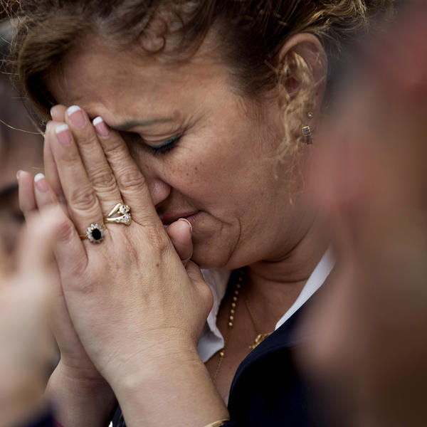 Pilar Cedeno, of Hackensack, N.J., prays as Mass is celebrated by Pope Francis is broadcast to crowds on the Benjamin Franklin Parkway from inside the Cathedral Basilica of Saints Peter and Paul, on Saturday in Philadelphia.