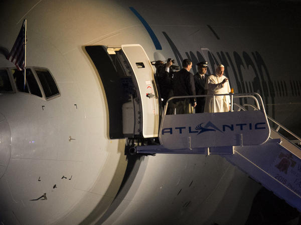 Pope Francis waves to the crowd at Philadelphia International Airport before departing for Rome on Sunday evening.