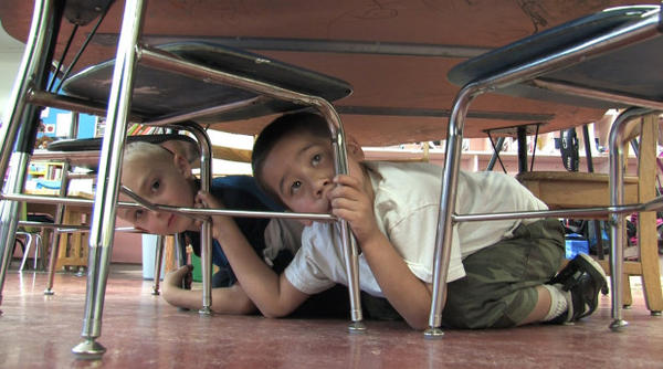 <p>This image shows kindergartners ducking and taking cover under their desk at the Blossom Gulch Elementary School during a tsunami drill Thursday, May 31, 2012, in Coos Bay, Ore.</p>