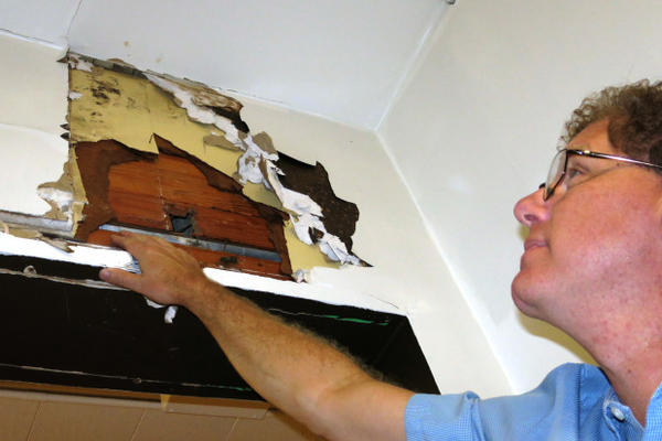 <p>Corbett School District superintendent Randy Trani inspects one of the crumbling walls at the Middle School.</p>