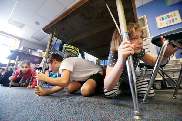 <p>Fifth graders Kashmir Pesicka, right, and Mason Stroud begin to get up after taking shelter under their classroom tables during an earthquake drill at West Woodland Elementary school October 17, 2013, in Seattle.</p>