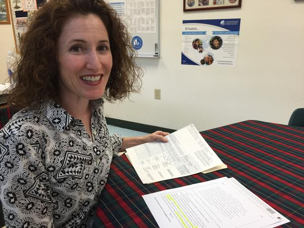 Miami teacher Brigette Kinney holds copies of her GRE scores and the state law creating the new teacher bonus program. She qualifies for the bonus of up to $10,000 but may not be able to complete the paperwork in time.