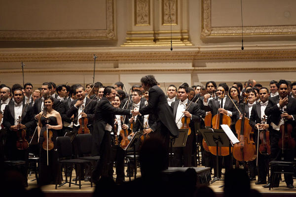 Gustavo Dudamel shakes hands with musicians after conducting the concert. He has a habit of plowing straight into the orchestra to congratulate his players.