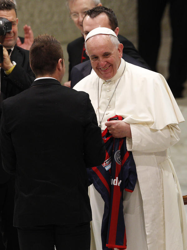 Pope Francis is given a San Lorenzo soccer team jersey by players at the Vatican in 2014.